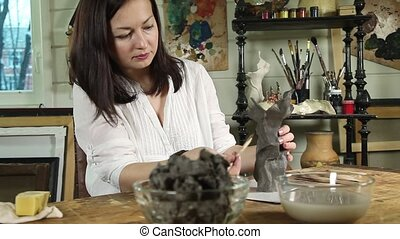 Artist woman sculpts from a clay - Dolly video shot of an...