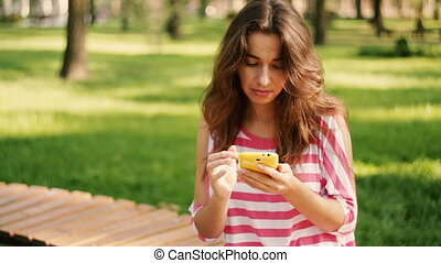 Young pretty woman write sms on phone against background of...