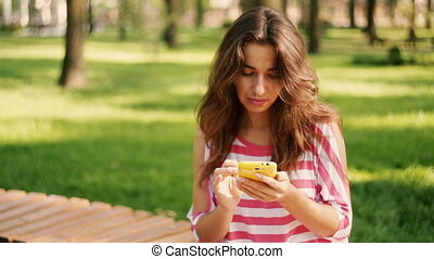 pretty woman write sms - Young smiling pretty woman write...