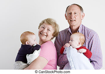 Happy grandparents holding twin boys
