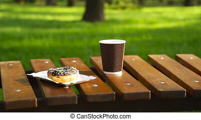 cup of latte and muffin on a park bench