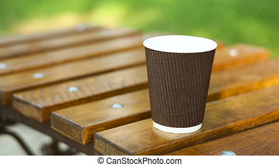 cup of latte on a bench in a summer park