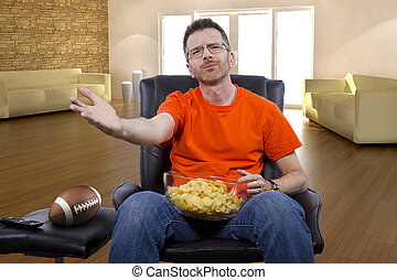 Male Watching Football with Snacks - Front view of man...