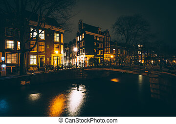 Bridge over a canal at night, in Amsterdam, Netherlands.