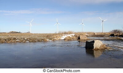 Wind farm and lake with boulder - Four wind turbines in a...