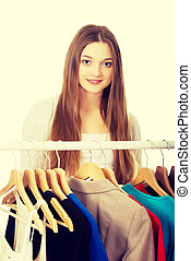 Teen woman thinking what to put on - Happy teen woman...