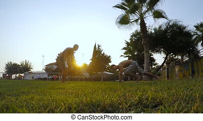 Two man man doing some push ups in a athletic field