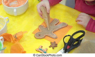 Close up of kid decorating the gingerbread cookies, Merry...