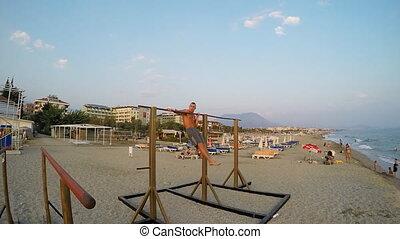 Man doing pull ups in beach.