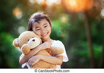 Little cute girl standing in the grass holding large teddy...