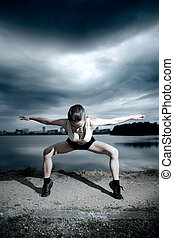 gymnast doing exercises near the water in the evening before the storm.