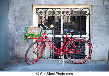red bicycle with flowers in a basket standing on the street...
