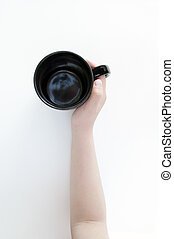 Black mug in hand isolated on a white background with...