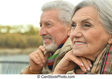 senior couple near river - Happy senior couple relax in...