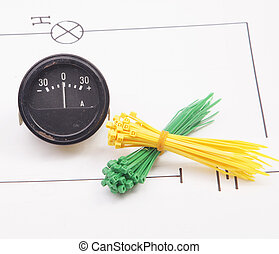 Ammeter and plastic ties on a background of the electric scheme