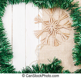 Christmas snowflake made of straw on a background of burlap...