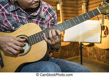 Close up of a man playing acoustic guitar
