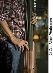 Close up of a man playing electric double bass.