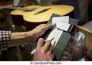 Customer signing on sale slip accept to buy guitar, shallow...