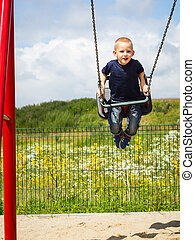 Child boy playing on swing outdoor - Little blonde boy...