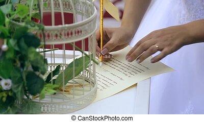 bride and groom put signatures on wedding ceremony