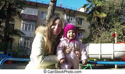 mother and daughter on a swing in the park in autumn sunny day. slow motion. Full HD
