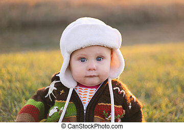 Adorable Baby Girl in Winter Hat and Sweater Outside