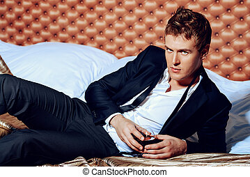 bedroom - Attractive handsome man in elegant suit lying on a...