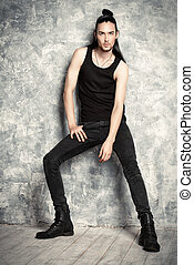 tall man - A tall, thin man brunette posing by the grunge...