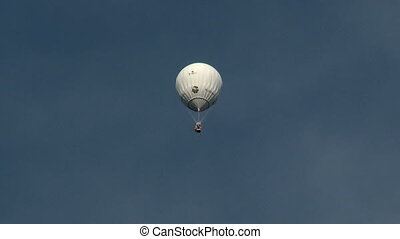 White hot air balloon floating in sky - View of white hot...