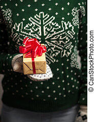 Girl holding a Christmas gift - Christmas gifts. Knitted...