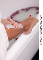 Pretty healthy girl is shaving her foot - Close up of leg of...