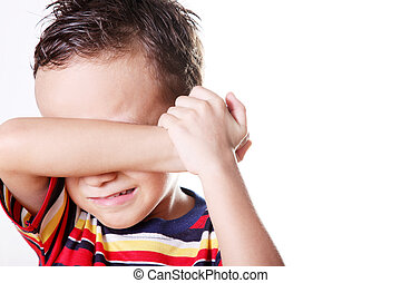 Cry - Child crying covering his face with his hand.