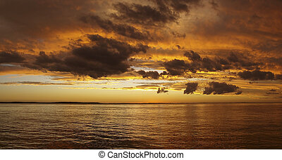 Multicolored golden sunrise over water - Gold,orange and...