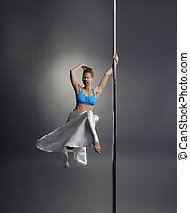 Lovely woman posing while dancing on pole