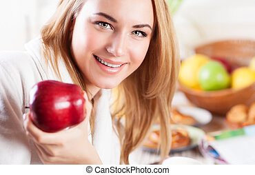 Happy woman eating apple
