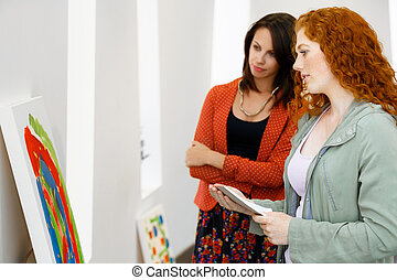 Young caucasian couple standing in a gallery and...