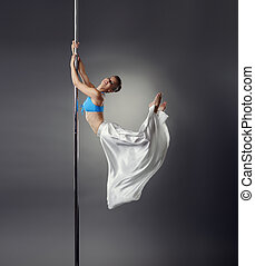 Pretty dancer bent elegantly while dancing on pole