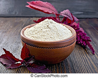 Flour amaranth in clay bowl on dark board - Amaranth flour...
