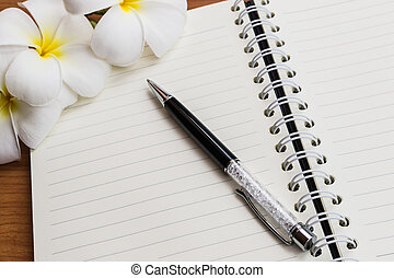 A pen and notebook with flower