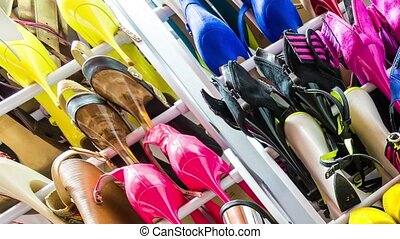 Rack with multicolored female shoes on heels