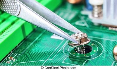 male hand unscrews screws tweezers on board computer