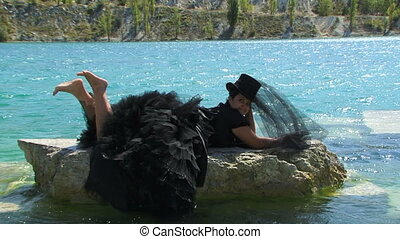 Woman In Black Lying On Rock At Lake - SLOW MOTION Side shot...