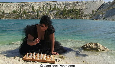 Young Woman In Black Playing Chess At Pond