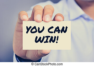 YOU CAN WIN !, message on the card held by a man hand,...