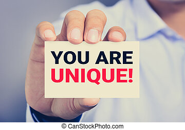 YOU ARE UNIQUE ! message on the card shown by a man hand