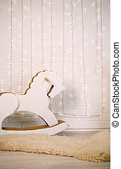 rocking horse in the backdrop of a brick wall with a garland...