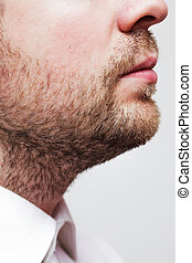 man with a three-day unkempt unshaven stubble in white shirt...