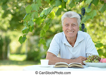 Older man with book - Handsome older man sitting at a table...