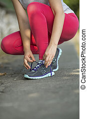 sports girl tying shoelaces - Young sports girl tying...